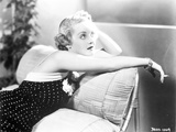 Bette Davis sitting on the Couch while Smoking a Cigarette in Black Sleeveless Polka Dot Dress Photo by  Movie Star News