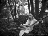 Veronica Carlson a white, chiffon, ruffled robe, while laying on the ground in the forest Photo by  Movie Star News