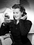 Janis Paige sitting on a Couch in Black Long Sleeve Velvet Dress with Mirror on the Right Hand Photo by  Movie Star News