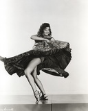 Jane Russell Posed in Black Velvet Dress while Swinging the Hips with Elbows Up and Knees Bent Photo by  Movie Star News