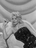 Jayne Mansfield sitting on the White Silk Couch in Black Sequin Strapless Dress and Pearl Necklace Photo by Bert Six