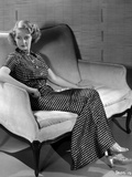 Bette Davis Seated on a White Couch Photo by Elmer Fryer