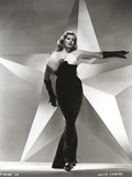 Anita Ekberg Pointing Her Left Hand with a Huge Star in Background in Classic Portrait Photo by  Movie Star News