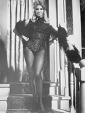 Angie Dickinson standing Near the Stairs wearing a Gilttering Dress in Black and White Photo by  Movie Star News