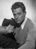 William Holden Posed in Classic Sweater while Holding a Black Coat Photo by AL Schafer