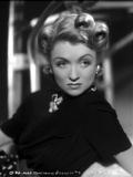 Constance Bennett on a Turtle Neck Top with Brooch sitting and Leaning Portrait Photo by  Movie Star News