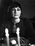 Anjelica Huston sitting at the Dining Table wearing a Loop Earring Portrait in Classic Photo by  Movie Star News