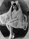 Claudette Colbert sitting on Bed, wearing White Dress with Veil Photo by  Movie Star News