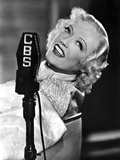 Marion Davies smiling in A Portrait Behind A Microphone in Black and White Photo by  Movie Star News