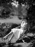 Claudette Colbert sitting on Chair, wearing White Dress Photo by  Walling