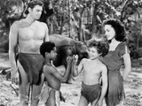 Johnny Weissmuller standing with Two Kids and a Woman in a Movie Scene Photo by  Movie Star News