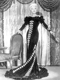 Mae West standing in Black Long Gown with Arm's Open Photo by  Movie Star News
