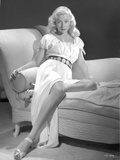 Gloria Grahame Siting on Table wearing Silver Gown Photo by  Movie Star News