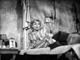 Anne Baxter on Printed Top sitting and Leaning on a Bed Photo by  Movie Star News