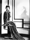 Anna Wong sitting on the Chair, wearing a Long Gown Photo by  Movie Star News