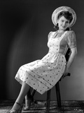 Anne Baxter on Printed Top sitting and smiling Photo by  Movie Star News