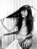 Anna Wong sitting on a Chair and Fixing Her Hair Photo by  Movie Star News