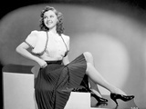 Susan Hayward sitting in Black Skirt and Shoes Photo by  Movie Star News