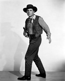 Jon Hall standing in Cowboy Outfit With Pistol Photo by  Movie Star News