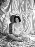 Mary Brian sitting in a White Shiny Dress in Photo by  Movie Star News