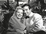 Alice Faye with a Guy sitting on a Becnh Photo by  Movie Star News