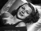 Rita Hayworth Lying and smiling on Bed Photo by A.L. Schafer