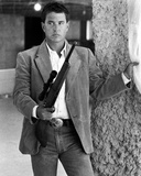 Tom Berenger standing in Coat With Rifle Photo by  Movie Star News