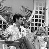 George Hamilton sitting on Chair With Doll Photo by  Movie Star News