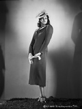 Rita Hayworth standing in Dress and Hat Photo by A.L. Schafer