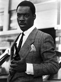 Eddie Murphy Holding Pistol in Tuxedo Photo by  Movie Star News