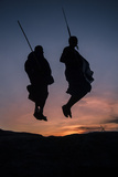 Two Masaai Warriors Silhouetted Performing Traditional Jump - Leap Kopje at Sunset Photographic Print by Nick Garbutt