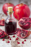 Glass Bottle with Pomegranate Juice and Pomegranates Photographic Print by Jana Ihle
