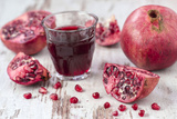 Pomegranates and Glass with Pomegranate Juice on White Wooden Table Photographic Print by Jana Ihle