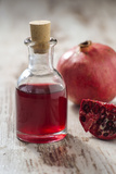 Glass Bottle with Pomegranate Juice and Pomegranate Photographic Print by Jana Ihle