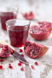 Sliced Pomegranates, Cores and Glass with Pomegranate Juice Photographic Print by Jana Ihle