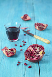 Sliced Pomegranate and a Glass of Pomegranate Juice on Turquoise Wooden Table Photographic Print by Jana Ihle