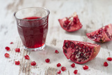 Pomegranate Pieces and a Glass of Pomegranate Juice on White Wooden Table Photographic Print by Jana Ihle