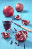 Whole and Sliced Pomegranate and Glass of Pomegranate Juice on Turquoise Wooden Table Photographic Print by Jana Ihle