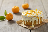 Small Orange Cake with White Icing on Wooden Table Photographic Print by Jana Ihle