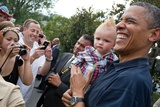 President Barack Obama Holds a Baby During an White House Independence Day Celebration Photo