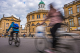 Cyclists Passing the Sheldonian Theatre, Oxford, Oxfordshire, England, United Kingdom, Europe Photographic Print by John Alexander