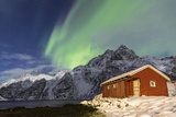 Northern Lights (Aurora Borealis) Illuminate Snowy Peaks and Wooden Cabin on a Starry Night Photographic Print by Roberto Moiola