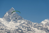 A Paraglider Hangs in Air with Dramatic Peak of Machapuchare (Fishtail Mountain) in Distance Photographic Print by Alex Treadway