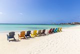 A Row of Colourful Wooden Deckchairs on Palm Beach, Aruba, Netherlands Antilles Photographic Print by Jane Sweeney