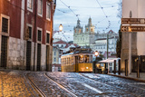 Romantic Atmosphere in Old Streets of Alfama with Castle in Background and Tram Number 28 Fotografiskt tryck av Roberto Moiola