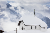 Clouds Above the Mountain Huts and Church Covered with Snow, Bettmeralp, District of Raron Photographic Print by Roberto Moiola