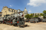 A Vintage Steam Train in a Restoration Yard with Dome of Former Parliament Building in Background Photographic Print by Sean Cooper