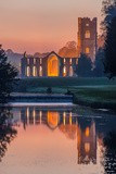 The Cistercian Monastery of Fountains Abbey Lit at Dusk and Reflected in the River Skell Photographic Print by Garry Ridsdale