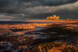 A Storm Passes Behind Bamburgh Castle with Last Light of Day Illuminating Rocky Shoreline Photographic Print by Garry Ridsdale
