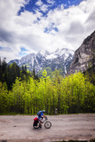 A Lone Cyclist Travels Along a Mountain Road with Trees and the Julian Alps in the Background Photographic Print by Sean Cooper